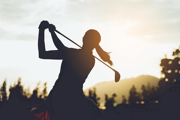 Silhouette d'une jeune joueuse de golf frappant de plein fouet et conservant le parcours de golf faisant du swing de golf, elle fait de l'exercice pour se détendre, ton vintage