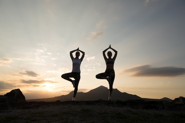 Silhouette de jeunes femmes pratiquant le yoga ou le pilates au coucher ou au lever du soleil dans un bel endroit de montagne.