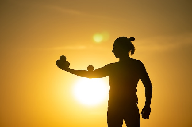 Silhouette de jongleur avec des balles sur le coucher du soleil coloré.