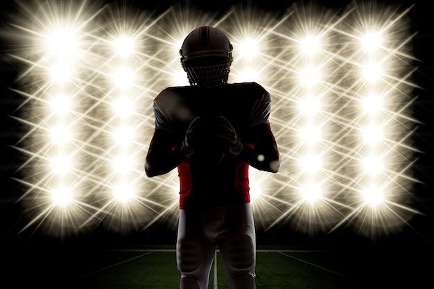 Silhouette d'un joueur de football avec un uniforme rouge devant les lumières.