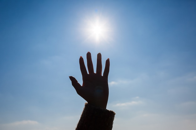 Silhouetté une main féminine contre un ciel bleu et un soleil éclatant