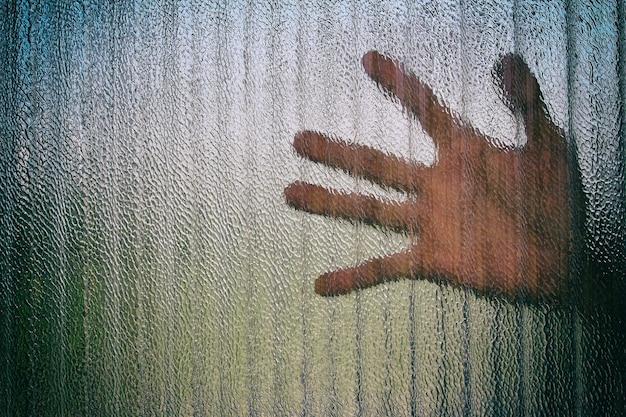 Silhouette d'une main sur une porte à travers une porte vitrée fermée.