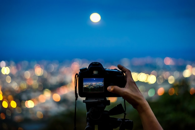 Silhouette de la main prenant une photo avec un appareil photo reflex numérique sur trépied dans la ville lumière de nuit des montagnes
