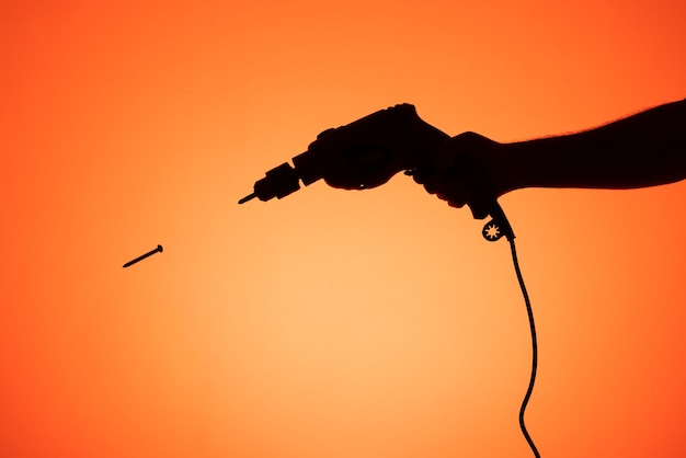 Silhouette d'une main tenant une perceuse avec une vis flottante