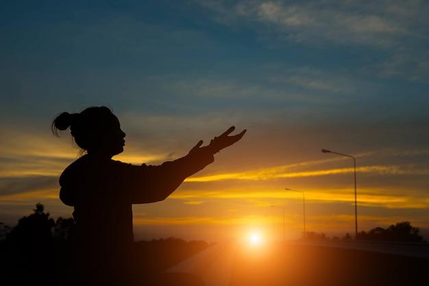 Silhouette de mains de femme avec la lumière du coucher du soleil
