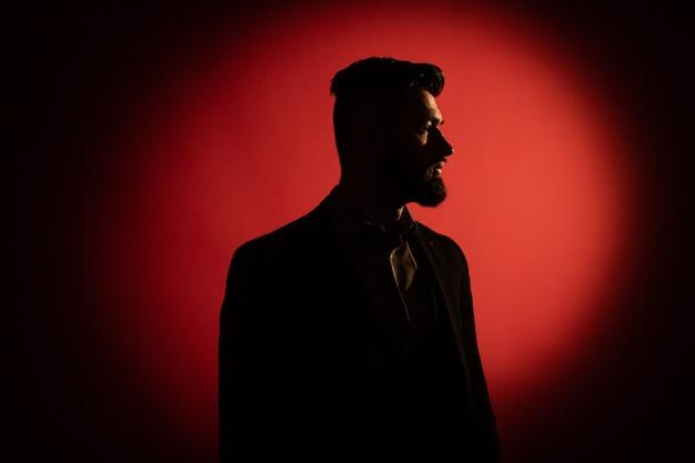 Silhouette masculine sombre. silhouette d'homme à barbe sur fond rouge avec espace de copie