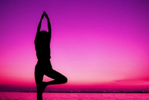 Silhouette, méditation, yoga, pose, pratique femme, sur, plage, coucher soleil, fond