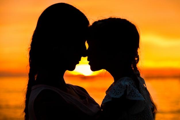 Silhouette de mère et fille sur coucher de soleil