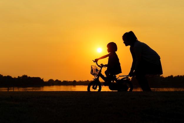Silhouette d'une mère qui apprend à sa fille à faire du vélo.