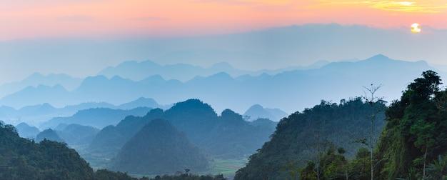 Silhouette de montagne magnifique paysage brume et brouillard dans les vallées au coucher du soleil