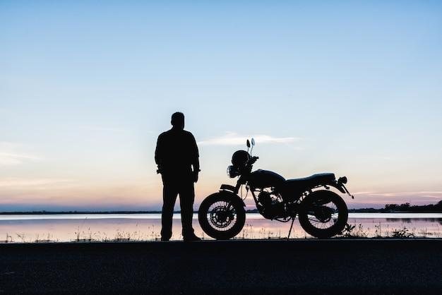 La silhouette d'un motard debout des voyageurs de loisirs et de la moto sur la route