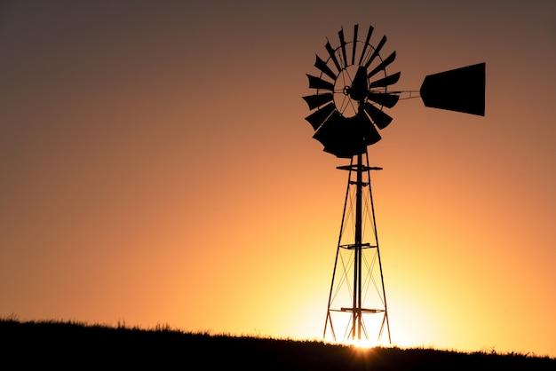 Silhouette d'un moulin à vent pendant le coucher du soleil