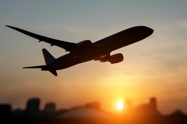 Silhouette noire d'un avion au-dessus de la ville. le coucher du soleil