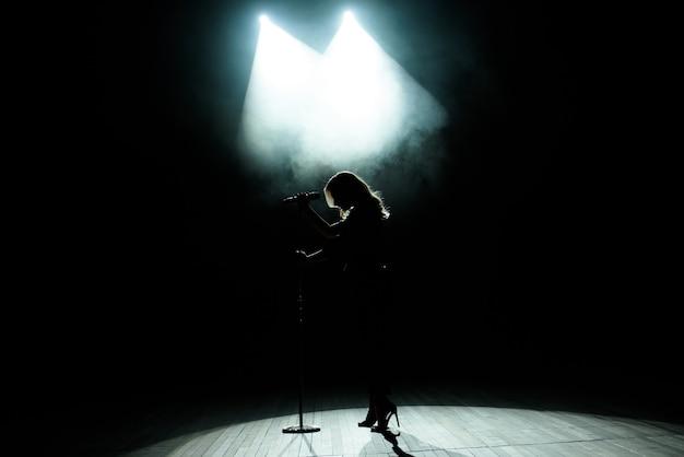 Silhouette noire de chanteuse avec des projecteurs blancs en arrière-plan.