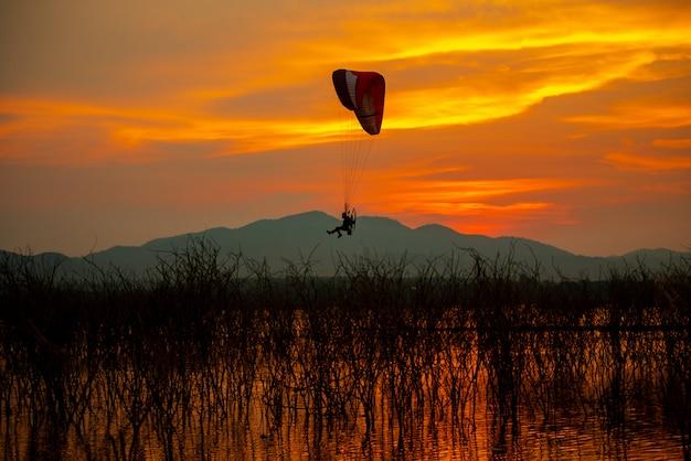 Silhouette oiseaux volants et paramoteur ciel coucher de soleil