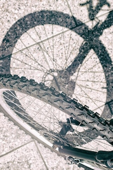 Silhouette d'ombre de roue avant de vélo et vue de pneu sur la surface en béton urbaine verticale