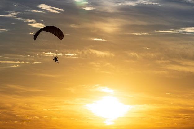Silhouette de parapente avec un beau fond de ciel et de soleil.