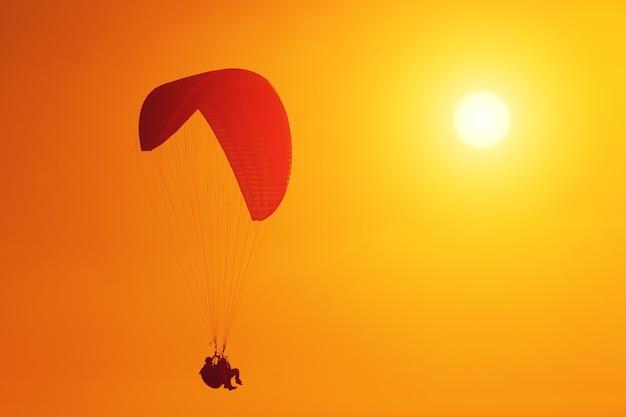 Silhouette de parapente planant au coucher du soleil
