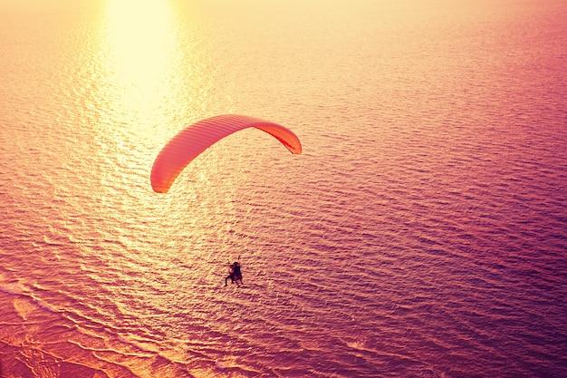 Silhouette de parapente planant au-dessus de la mer au coucher du soleil