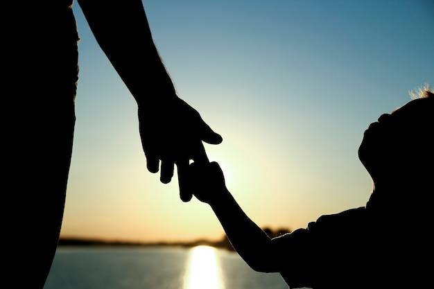 Silhouette le parent tient la main d'un petit enfant