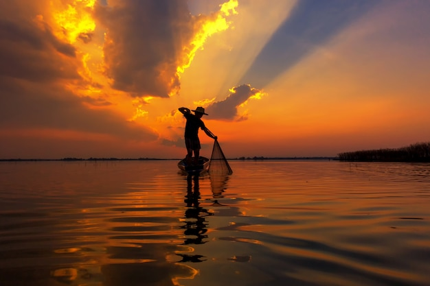 Silhouette de pêcheur au coucher du soleil