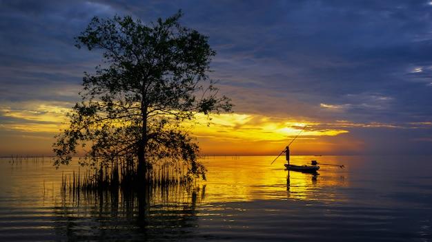 Silhouette de pêcheur en bateau avec arbre de mangrove dans le lac sur le lever du soleil.