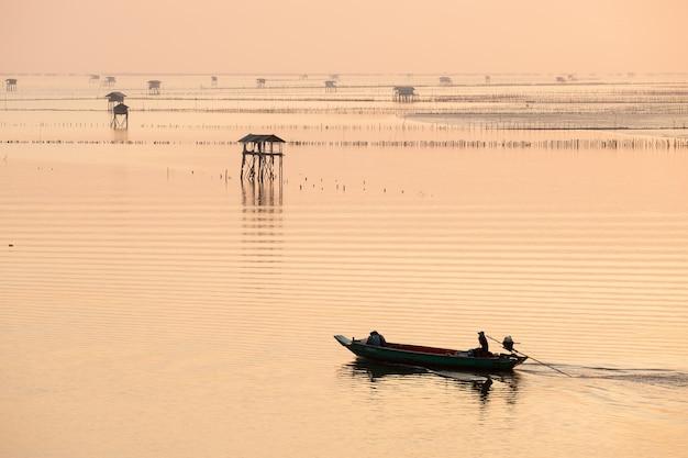 Silhouette de pêcheur en bateau en mer à bang taboon bay, au sud de la thaïlande