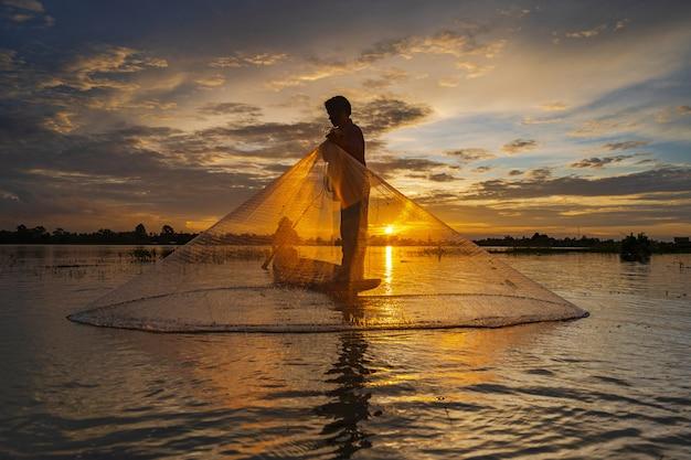 Silhouette de pêcheur sur un bateau de pêche avec filet sur le lac au coucher du soleil