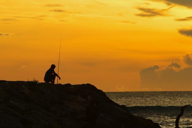 Silhouette de pêcheur et de coucher de soleil