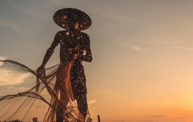 Silhouette de pêcheur de filets de pêche sur le bateau.