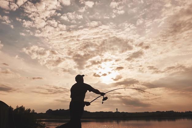 Silhouette de pêcheur jette une canne à pêche dans le lac au coucher du soleil