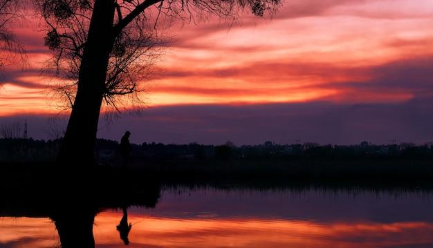 Silhouette d'un pêcheur sur le lac dans le contexte d'un coucher de soleil spectaculaire.