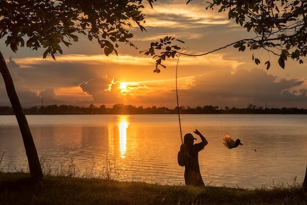Silhouette de pêcheur pêchant au bord de la rivière au coucher du soleil