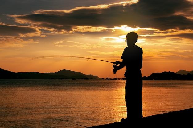 Silhouette de pêcheur pêchant sur la plage au coucher du soleil