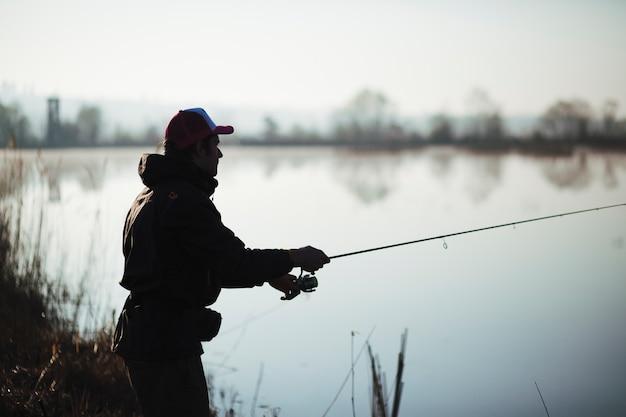 Silhouette, de, a, pêcheur, peche, sur, lac