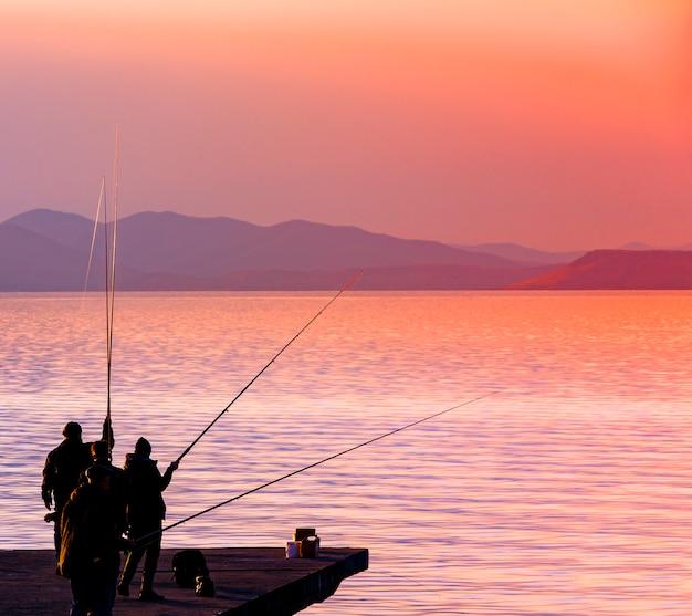 Silhouette de pêcheurs pêchant au coucher du soleil sur la mer