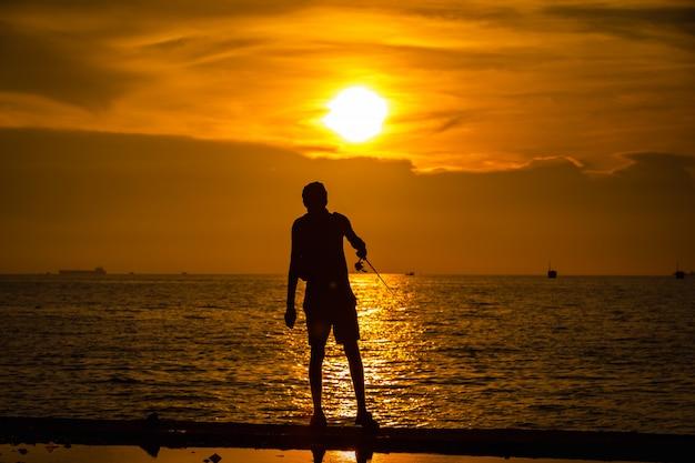 Silhouette de pêcheurs de portrait de vie sur la mer et le coucher de soleil sur fond de temps en soirée