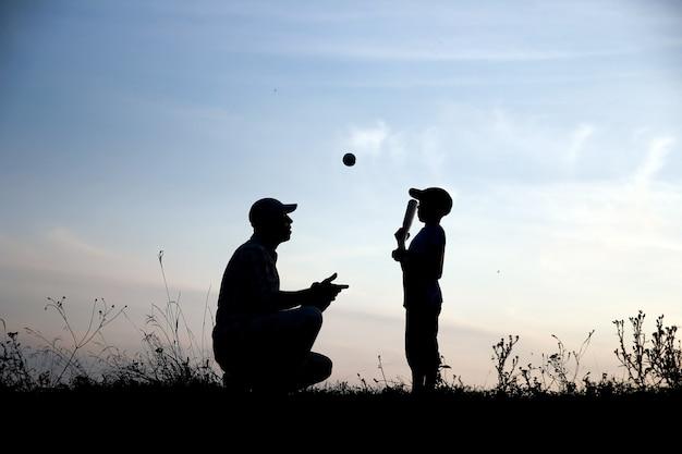 Silhouette de père et fils jouant au baseball sur le concept de sport familial nature