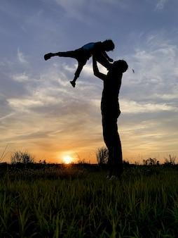 Silhouette, père, porter, fils, contre, ciel, pendant, coucher soleil