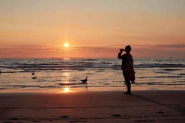 Une silhouette d'une personne buvant sur un bord de mer au coucher du soleil