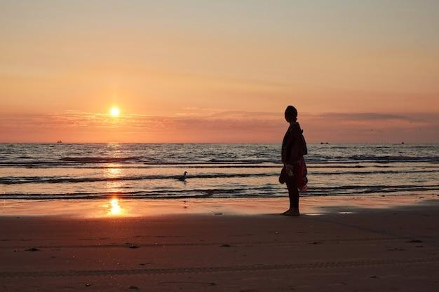 Une silhouette d'une personne debout sur un bord de mer au coucher du soleil