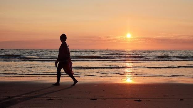 Une silhouette d'une personne marchant sur un bord de mer au coucher du soleil
