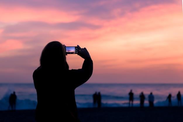Silhouette d'une personne, une photo du coucher de soleil sur un smartphone