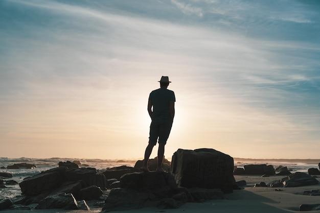 Silhouette d'une personne sur la plage rocheuse au coucher du soleil