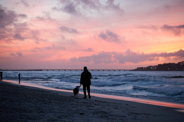 Silhouette d'une personne promenant son chien sur une plage un jour avec un coucher de soleil rouge