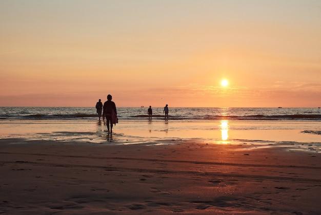 Une silhouette de personnes marchant sur un bord de mer au coucher du soleil