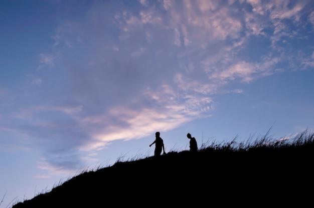 Silhouette de personnes marchant sur la colline à la montagne