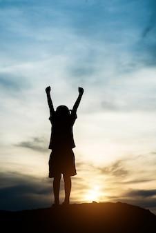 Silhouette, de, petite fille, élever main, à, temps heureux liberté