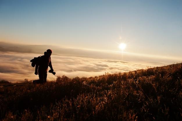 Silhouette de photographe homme avec caméra sur fond de main montagnes sur coucher de soleil avec brouillard