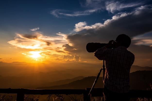 Silhouette d'un photographe de paysage utiliser super téléobjectif au sommet des montagnes pendant le ciel coucher de soleil